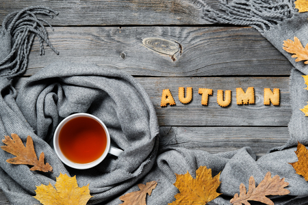 Autumn composition, fall leaves, hot steaming cup of tea and a warm scarf on wooden table background.