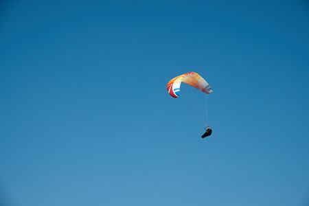 Paraglider is flying in the blue sky. Paragliding in the sky on a sunny day