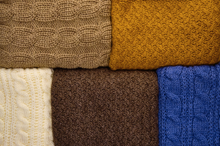 Stack of Warm knitwear close-up. Woolen knit texture as background