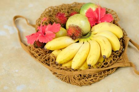 Banana Rambutan Flower Composition Top Down View. Tropical Detox Fruit in Basket Flatlay Above Shot. Organic Sweet Vegetarian Breakfast for Vacation Lifestyle. Ripe Fresh Summer Food Stock Photo