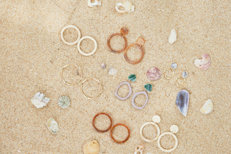 Handmade Jewelry on Sand Beach Top Down View. Travel Cheap Jewels Souvenir on Sea Shell Background. Craft Summer Earring and Stone Ring for Fashion Gift. Aquamarine Beautiful Decoration Set