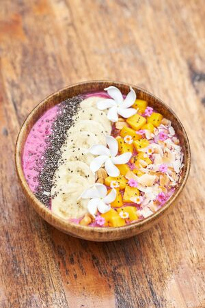 Tropical Breakfast Fruit Smoothie Bowl. Healthy Mango and Banana Food in Wooden Bowl on Table. Exotic Vegan Fresh Drink with Flower Decoration. Morning Cocktail Dessert