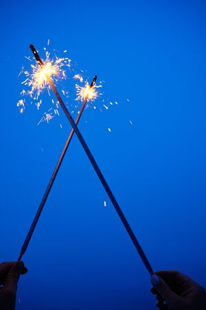 Pairs of Hand Holding and Crossed Burning Sparkler Isolated on Evening Blue Sky Background. Arm Silhouette Festive Firework for Celebration Happy New Year. Glittering Bengal Flame Light