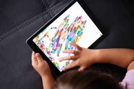 Preschool Girl Draws on the Tablet. Little girl play with tablet.