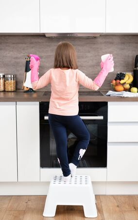 Preschool Girl make Cleaning Induction Hob. Washing a kitchen in pink gloves with a pink Sponge and Detergent. Cleaning concept
