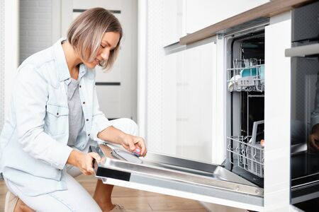 Woman Put Soap Tablet in Dishwasher box. Dishwasher with Dirty Dishes. Washing dishes in the kitchen
