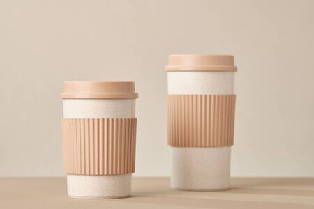 Two Eco Coffee Cup Isolated on Beige Background Closeup Copy Space Photo. Stylish Paper Container Different Size for Morning Hot Energy Drink. Disposable Eco-friendly Cardboard Mugs for Beverages Archivio Fotografico - 133481845