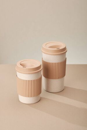 Two Eco Coffee Cup Isolated on Beige Background Closeup Copy Space Photo. Stylish Paper Container Different Size for Morning Hot Energy Drink. Disposable Eco-friendly Cardboard Mugs for Beverages Archivio Fotografico - 133481869