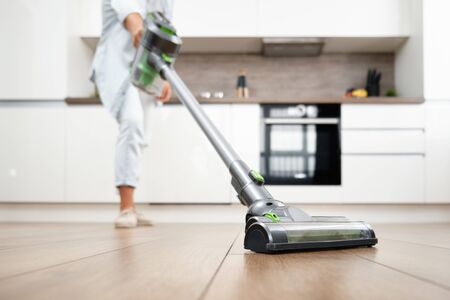 A Young Woman Vacuuming the Floor. Cleaning in the House. Vacuum Cleaner in kitchen. 스톡 콘텐츠