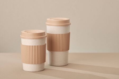 Two Eco Coffee Cup Isolated on Beige Background Closeup Copy Space Photo. Stylish Paper Container Different Size for Morning Hot Energy Drink. Disposable Eco-friendly Cardboard Mugs for Beverages Archivio Fotografico - 133483117