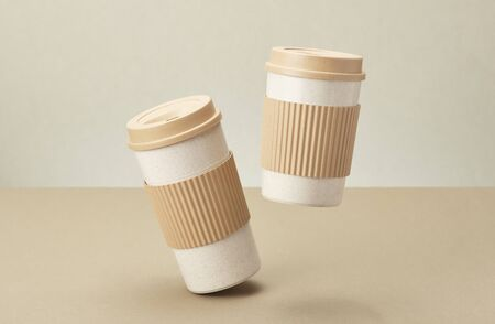 Two Eco Coffee Cup Isolated on Beige Background Closeup Copy Space Photo. Stylish Paper Container Different Size for Morning Hot Energy Drink. Disposable Eco-friendly Cardboard Mugs for Beverages Archivio Fotografico - 133483305