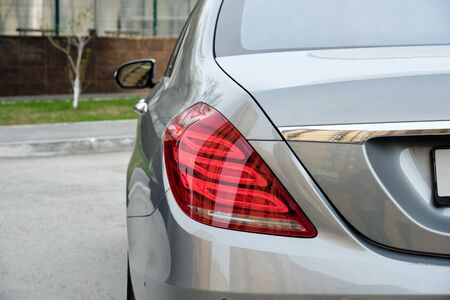 Business Class Luxury Elegant Car Closeup Photo. Parking Modern Prestige Grey Sedan Automobile on Asphalt Concrete Street Road. Back Body Detail Taillight and Bumper, Trunk, Glass and Mirror