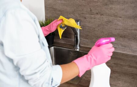 Woman doing Cleaning Kitchen. Washing a kitchen in pink gloves with a yellow Sponge and Detergent . House cleaning