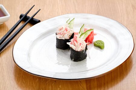 Japanese Sushi Rolls with Crab Meat and Cucumber, Ginger and Wasabi on White Plate. Soy Sauce in Bowl and Eating Sticks on Wooden Table. Healthy Oriental Rice Dish Meal Food Closeup Photo