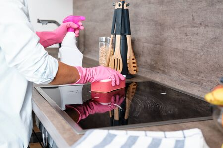 Cleaning Induction Hob. Washing a kitchen in pink gloves with a pink Sponge and Detergent. Cleaning service concept