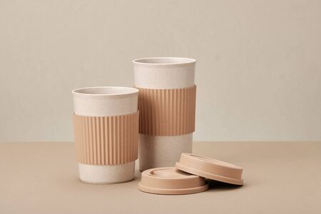 Two Eco Coffee Cup Isolated on Beige Background Closeup Copy Space Photo. Stylish Paper Container Different Size for Morning Hot Energy Drink. Disposable Eco-friendly Cardboard Mugs for Beverages Archivio Fotografico - 133483670