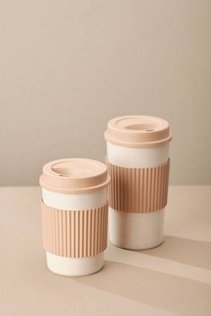 Two Eco Coffee Cup Isolated on Beige Background Closeup Copy Space Photo. Stylish Paper Container Different Size for Morning Hot Energy Drink. Disposable Eco-friendly Cardboard Mugs for Beverages Archivio Fotografico - 133483618