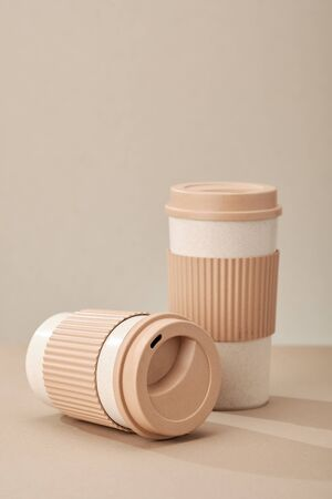 Two Eco Coffee Cup Isolated on Beige Background Closeup Copy Space Photo. Stylish Paper Container Different Size for Morning Hot Energy Drink. Disposable Eco-friendly Cardboard Mugs for Beverages Archivio Fotografico - 133483628