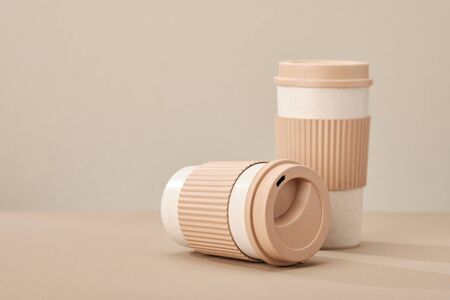 Two Eco Coffee Cup Isolated on Beige Background Closeup Copy Space Photo. Stylish Paper Container Different Size for Morning Hot Energy Drink. Disposable Eco-friendly Cardboard Mugs for Beverages Archivio Fotografico - 133483255