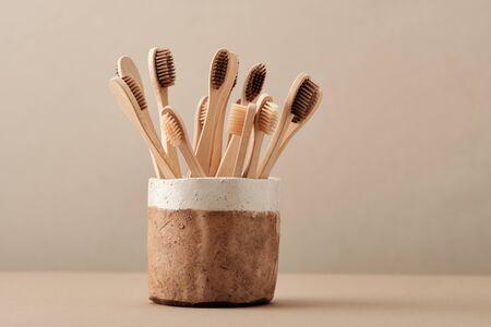 Cepillo de dientes ecológico de madera en taza de cerámica marrón Copie el espacio plano Lay. Colección de elegante accesorio de baño ecológico Clear Healthcare para dientes limpios