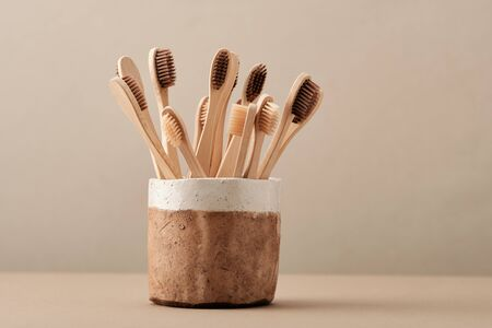 Wooden Eco Toothbrush in Brown Ceramic Cup Copy Space Flat Lay. Collection of Elegant Ecological Clear Healthcare Bath Accessory for Clean Teeth