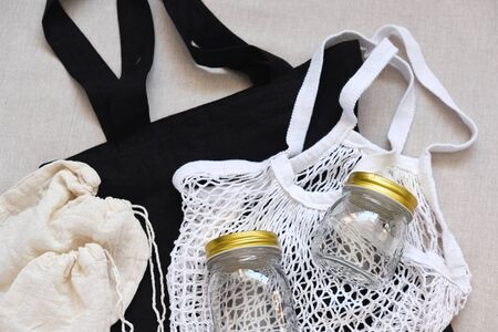 Closed Golden Cap Glass Bottle Lying on String Bag, Perhaps-bag, Empty Knotted Pouches on Black Shopping Sack Isolated on White Fabric Textile Background Top View. Classical Package Collection 免版税图像