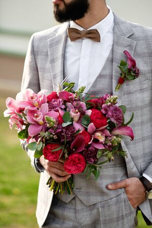 Man Clothed Stylish Suit Holding Bouquet of Flower. Bearded Character Caucasian Young Male Wearing Elegant Bow Tie, White Shirt and Fashion Jacket Decorated Boutonniere. Barbate Groom Looking Away