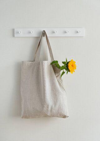 Junge gelbe Sonnenblume in Textil-Eco-Tasche hängend am Haken isoliert auf weißem Wandhintergrund Textfreiraum. Leere Leinwand recyceln wiederverwendbaren Einkaufssack. Verpackung aus natürlichem organischem Material