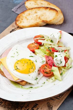 Fried Egg on Sandwich Toast Bread Top Down View. Healthy English Breakfast with Tomato Salad and Ham. Vegetable Morning Food Snack. Traditional Roasted Crispy American Meal Closeup