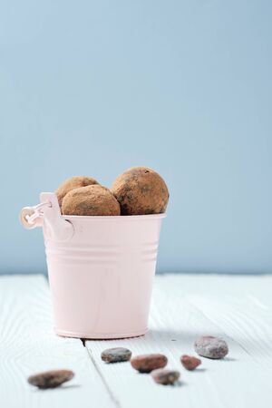 Sweet Chocolate Balls in Bucket for Rawfoodist. Yummy Natural Healthy Truffles with Cocoa Powder. Vegan Food Dessert Concept. Practice of Eating Uncooked Product. Side View Blue Background