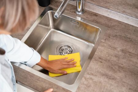 Woman Make Cleaning Kitchen Sink. Washing a kitchen with a yellow Sponge and Detergent. House cleaning