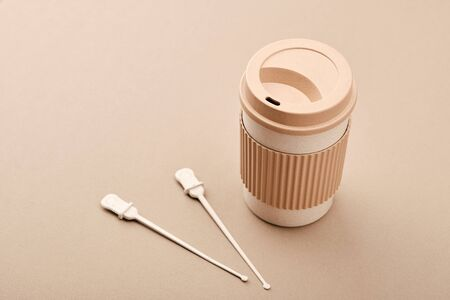 Eco Coffee Cup Isolated on Beige Background Closeup Copy Space Photo. Stylish Paper Container Different Size for Morning Hot Energy Drink. Disposable Eco-friendly Cardboard Mugs for Beverages
