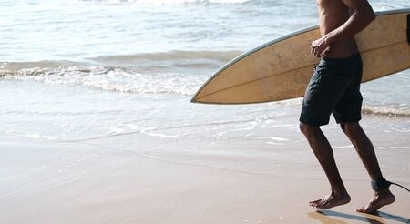 Man Surfer Sitting at Surfboard on Sand Beach. Happy Mulatto Guy Pose on Tropical Summer Ocean Coast with Blue Longboard. Extreme Water Sport Equipment for Summer Travel