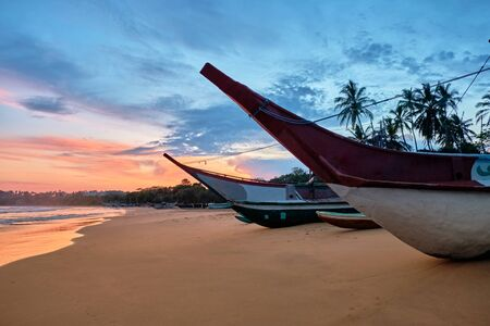 Blue Fishing Boat on Sand Ocean Beach at Sunset. Bright Vessel Full of Fishman Equipment Ready to Sail. Ship Stay on Coastline. Evening Green Palm Landscape. Marine Transport