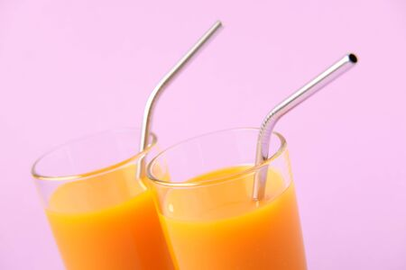 Two Orange Juice Glass with Metallic Steel Tubes Isolated on Purple Background Copy Space Photo. Alcohol Free Healthy Vitamin Fresh Drink. Tropical Beverage for Breakfast Standing on Violet Area