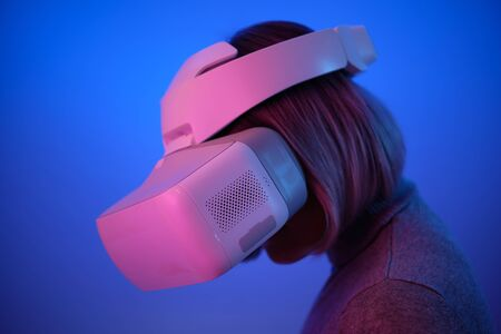 Young Woman Playing on Vr Glasses Touching Air During Virtual Reality Experience Isolated on Blue Background Copy Space Closeup Studio Photo. Girl Having Fun Time with Headset Goggles Stok Fotoğraf
