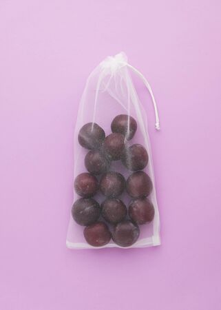 Natural Organic Plums in Shopping Net Bag Top View Isolated on Light Purple Background Copy Space. Fresh Tasty Ripe Fruit Food. Sweet Vitamin Delicious Nutrition Product Ingredient for Raw Food Eater