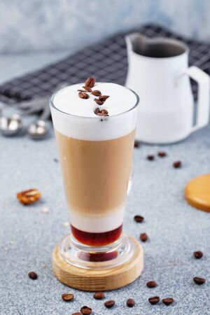 Latte Macchiato with Cocoa Powder and Coffee Beans in Glass Cup Standing on Wooden Desk. Pinscher Spoon and Towel on Background. Fresh Energy Aromatic Barista Morning Breakfast Drink