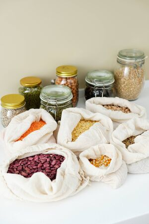 Corn Maize Bean Green Apple Ripe Apricot in Bag, Peanuts Nuts Peas Buckwheat in Closed Glass Bottle on Kitchen Table Isolated on Beige Wall Background Copy Space. Agricultural Food Full Pouch