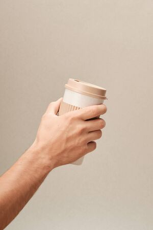 Eco Coffee Cup in Hand on Beige Background Closeup Copy Space Photo. Stylish Paper Container Different Size for Morning Hot Energy Drink. Disposable Eco-friendly Cardboard Mugs for Beverages