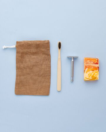 Toothbrush Retro Metallic Shaver Empty Brown Pouch and Decorative Yellow Orange Soap Isolated on Blue Background Copy Space Top View. Bath Accessory and Textile Fabric Bag. Everyday Using Care Items Stok Fotoğraf