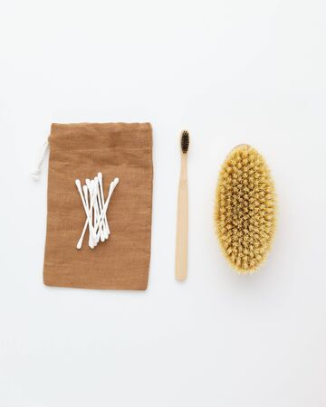 Wooden Toothbrush Brush Ear Sticks on Brown Bag Isolated on White Background Copy Space Flat Lay. Collection of Ecological Clear Healthcare Bath Accessories and Empty Textile Pouch Stok Fotoğraf