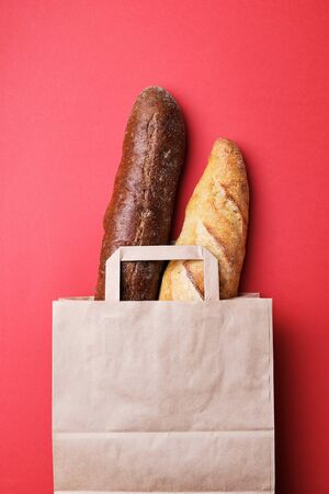 Fresh bread and baguette in paper bag on the red background. Bak
