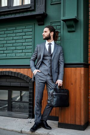 Attractive bearded young man in classic suit with bag.