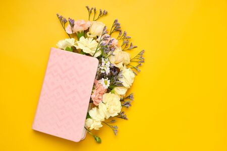Pink Notepad with Flowers over yellow background. Spring mood