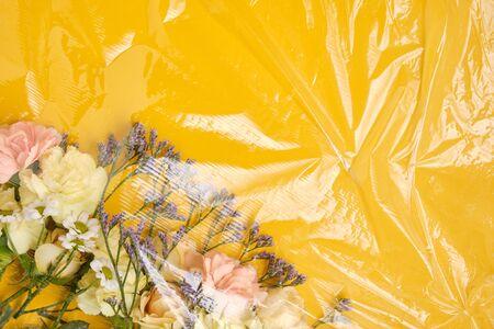 Flowers under a transparent film. Polyethylene Film. Plastic pollution and environmental problem