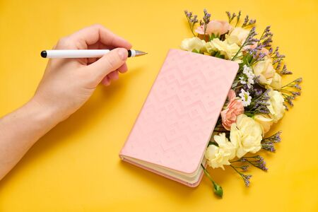 Pink Notepad with Flowers over yellow background. Spring mood. Girl writes plans