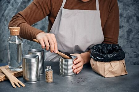 Young woman sowing seeds in metal cans.