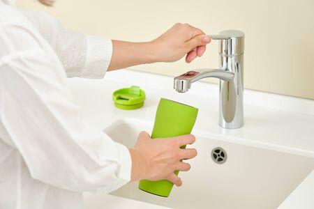 Woman dish washing a bottle. Running water 免版税图像