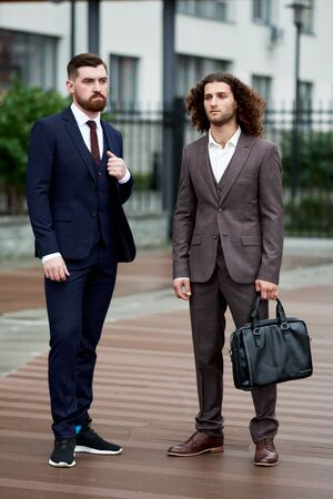 Attractive bearded young men in classic suit with bag. Elegancy and male style 免版税图像